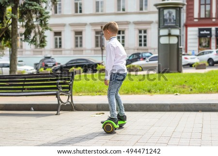 Stylish young boy riding a hover board in an urban park standing balancing on it facing the camera with a smile