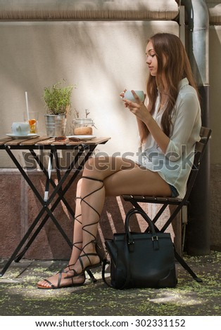 Stylish young brunette beauty having tasty refreshments in street coffee shop. - stock photo