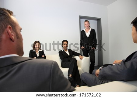 Stylish young business people sitting in a waiting room on comfortable sofas as they wait for a meeting or interview - stock photo