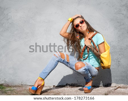 Stylish young girl posing against gray wall - stock photo