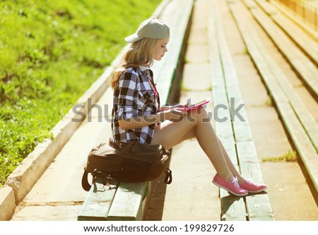 Stylish young girl with tablet pc resting in the city park - stock photo