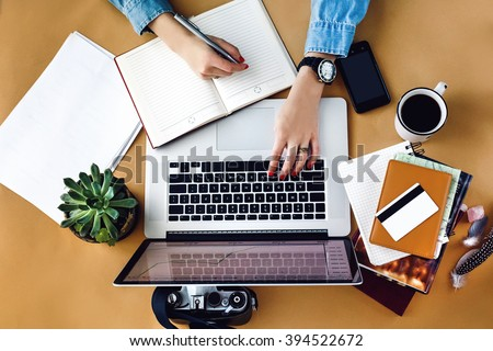 stylish young girl working  analytics holding pen on craft background with laptop and papers flat lay - stock photo