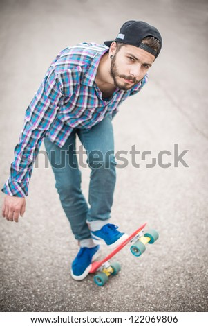 Stylish young guy on a red skateboard