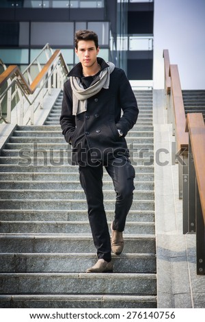 Stylish Young Handsome Man in Black Coat Standing in City Center Street with Skyscraper Behind Him, Looking to the Camera - stock photo