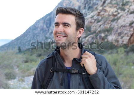 Stylish young handsome man standing on the precipice of the canyon. View from the front
