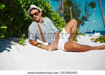 Stylish young male model man lying on beach sand  wearing hipster summer hat  enjoying summer travel holiday near the ocean in sunglasses - stock photo