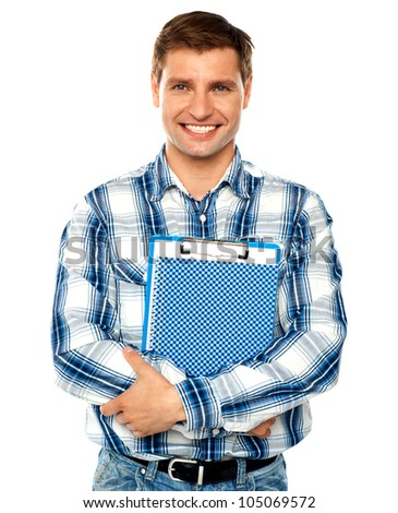 Stylish young man holding clipboard and notepad. Arms crossed - stock photo