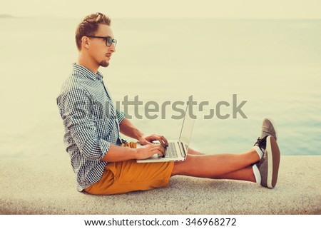 stylish young man in glasses with a beard shirt and shorts and sneakers working on laptop while sitting on the beach on the pier, sending mail, mounts, video editing and photography