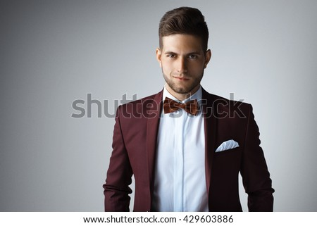 Stylish young man in suit and tie. Business style. Fashionable image. Office worker. Sexy man standing and looking at the camera - stock photo