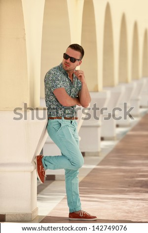 stylish young man leaning against yellow wall