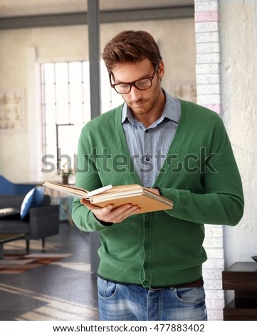 Stylish young man standing at home, reading book.