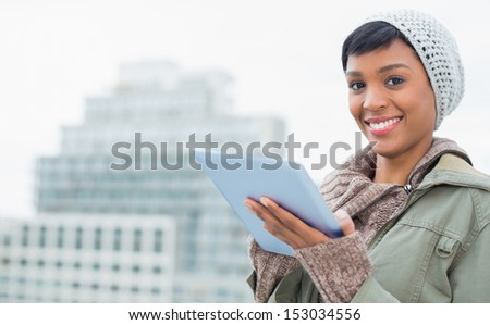 Stylish young model in winter clothes using a tablet pc outside on a cloudy day - stock photo
