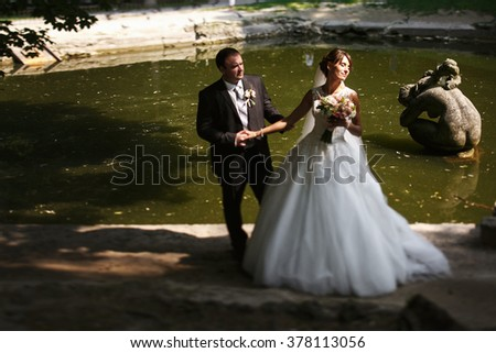 Stylish young newlyweds near the lake in the park