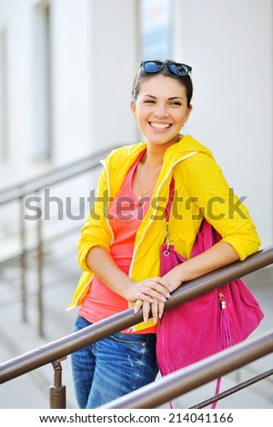 Stylish young smiling girl in colorful clothes - stock photo
