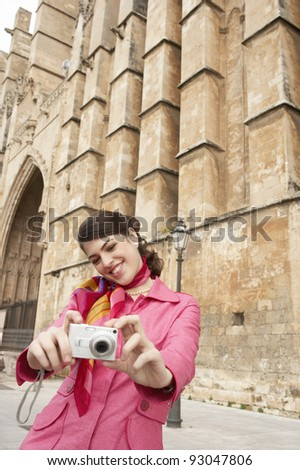 Stylish young tourist taking pictures near a monument. - stock photo