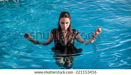 Stylish young wet woman in black dress standing in the water in a swimming pool
