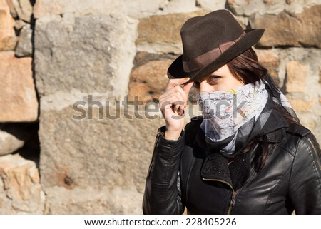 Stylish young woman bandit doffing her hat and looking at the camera with a scarf tied around her face concealing her features, against a stone wall with copyspace - stock photo