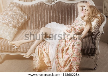 Stylish young woman in a vintage dress in a luxurious interior - stock photo