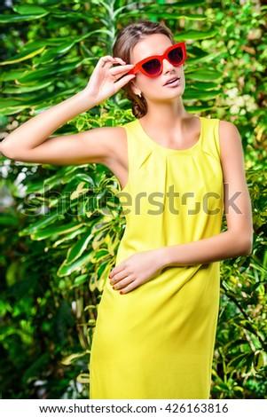 Stylish young woman in bright yellow dress and pin-up glasses enjoying summer. Beauty, fashion. - stock photo