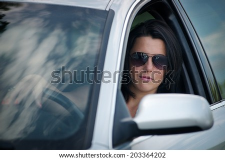 Stylish young woman in sunglasses driving a car looking through the open side window at the camera with a serious thoughtful expression