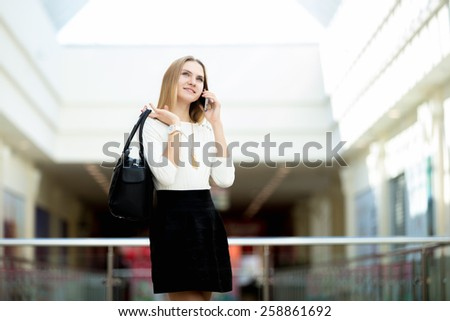Stylish young woman in trendy clothes out for shopping or business holding handbag, talking on cellphone, making a call with dreamy smile, copyspace - stock photo