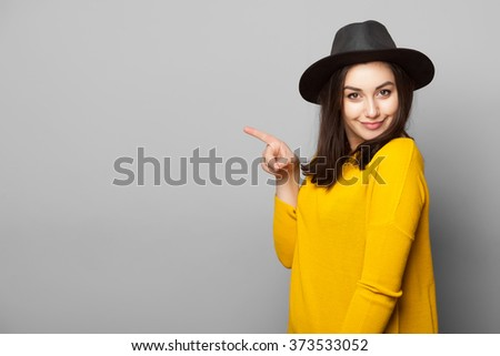 Stylish young woman pointing her finger towards blank space isolated over grey background - stock photo