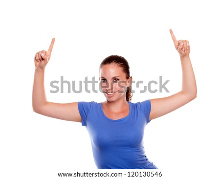 Stylish young woman pointing up and looking at you on blue shirt standing over white background - copyspace - stock photo