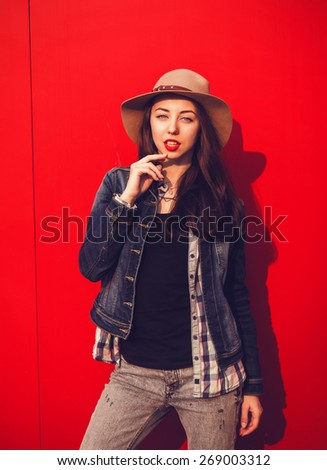 stylish young woman posing on a background of bright walls of the city - stock photo