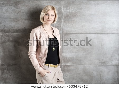 Stylish young woman standing against grey wall hands in pockets.