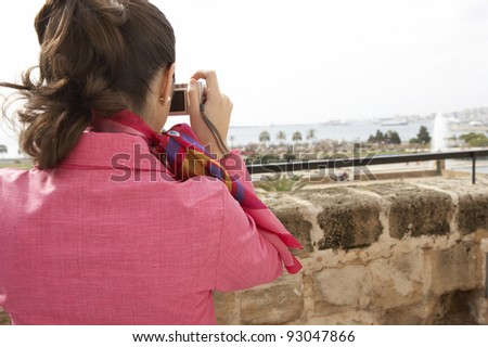 Stylish young woman taking pictures from a city observatory. - stock photo