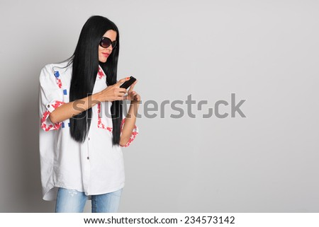 Stylish young woman with long black hair uses a cell phone. Girl twenty-six years. - stock photo