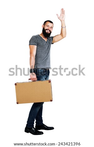 Stylishly confident. Handsome young bearded man holding a suitcase - stock photo