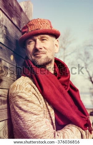 Stylishly dressed, bearded man in funny hat standing in a park in sunny day. Toned image.