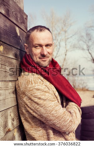 Stylishly dressed, bearded man standing in a park in sunny day, looking away and smiling. Toned image.