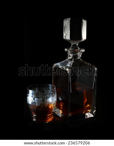 Stylishly lit brandy decanter and lead crystal glass against a black background. Copy space. - stock photo