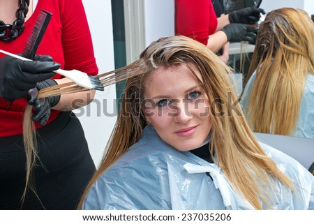 stylist coloring attractive woman hair in salon