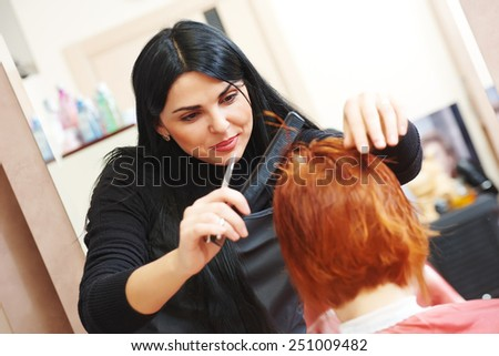 Stylist cutting hair of a female client at the beauty salon - stock photo