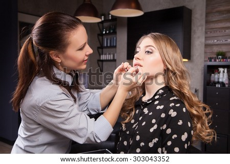 Stylist doing professional make up of young woman - stock photo