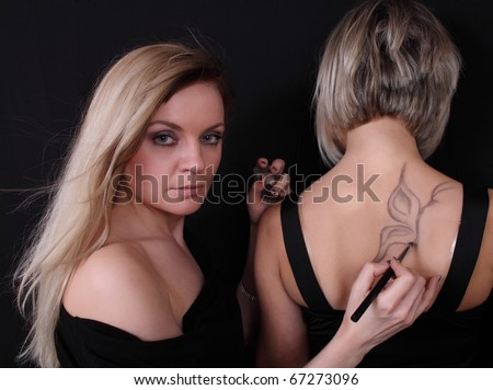 stylist draws a butterfly shadows on chpine woman - stock photo