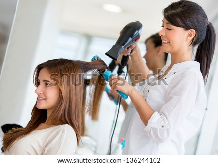 Stylist drying hair of a female client at the beauty salon - stock photo