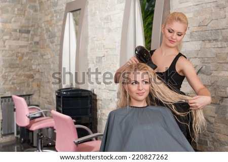 Stylist drying hair of female client at beauty salon. Young female beautician giving new hair style to woman at parlor  - stock photo