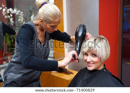 stylist drying woman hair in hairdresser salon - stock photo