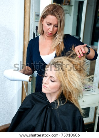 stylist drying woman hair with blower - stock photo