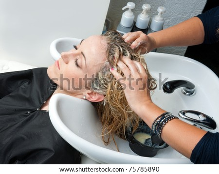 stylist putting color on woman hair in salon pool - stock photo