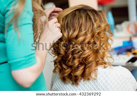 Stylist using curling iron for hair curls, close-up, shot in barber beauty salon