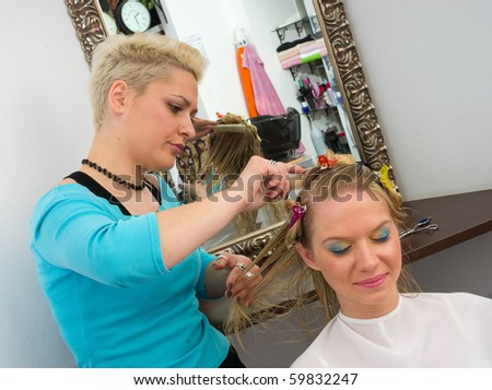 stylist work on woman hair in salon