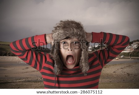 Stylistic Expressive Shocked boy with fur hat - with vintage vignetted effects  - stock photo