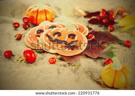 Stylized Halloween decor pumpkin cookies and assorted pumpkins. Popular American event party decorative dessert idea. - stock photo