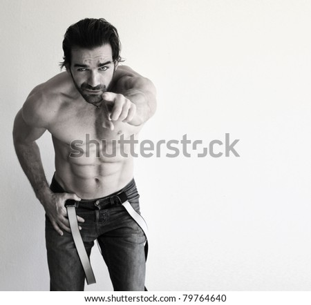 Stylized portrait of a fit young guy smirking and pointing at you against a neutral  background with copy space - stock photo