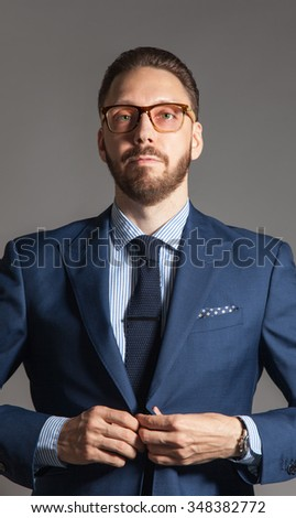 Suave handsome stylish bearded man with glasses in classic blue suit